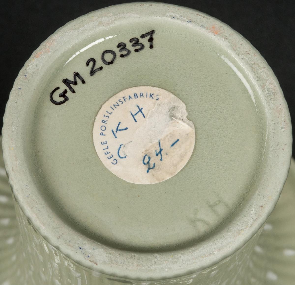 """Vas av flintgods, modell -KH, formgiven av Arthur Percy för Gefle Porslinsfabrik. Smal, cirkelformad buk med vertikal räffling, som utmynnar i en trattliknande överdel med mjukt böjda kanter. Dekor """"Celadon 2"""", ljust gröngrå fond täckt med vita stavar. Tryckt, ofärgat """"KH"""" i botten och fabriksetikett: """"KH, Celadon, 24""""."""