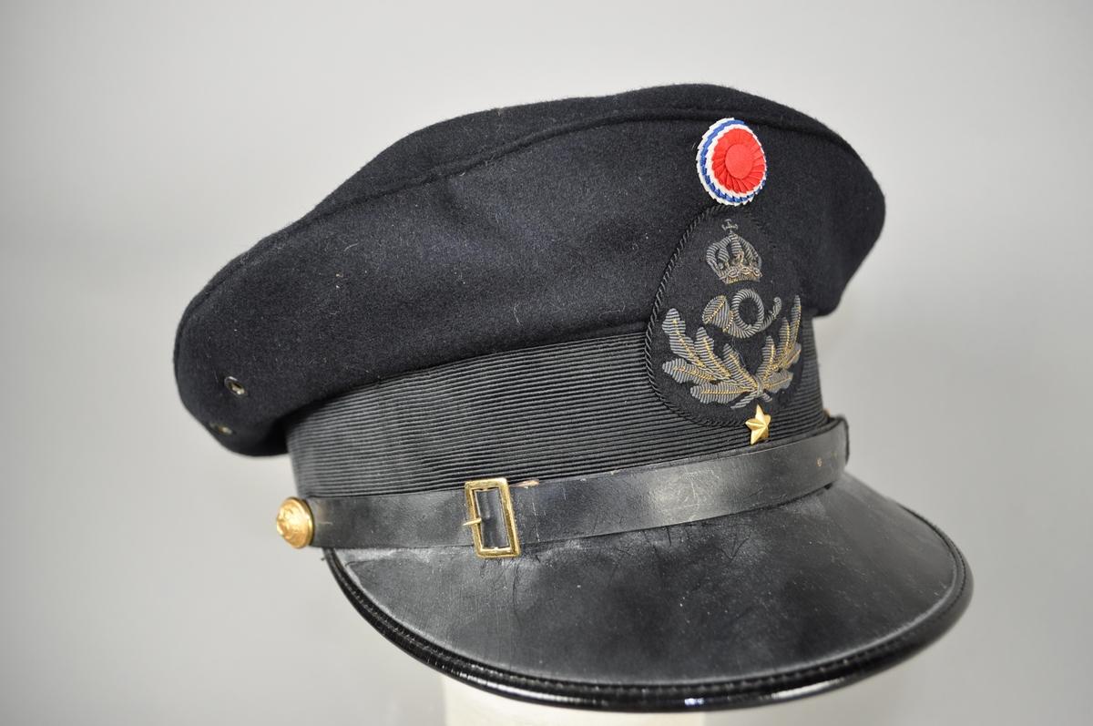Uniformslue med påsydd og gullbrudert posthorn med ekeløv. En stjerne og trokolor.