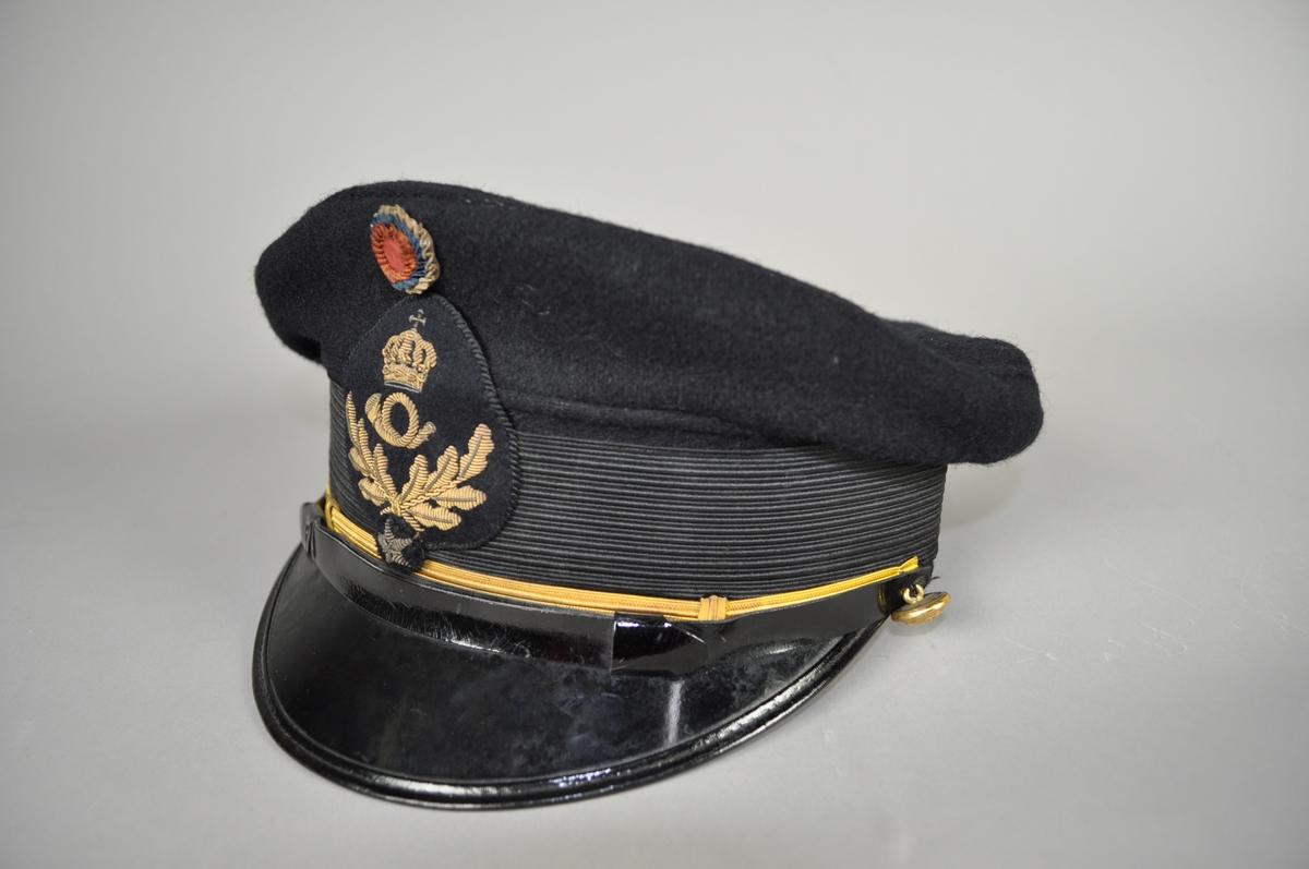 Uniformslue for postekspeditør med påsydd postemblem med ekeløv og 1 stjerne. Gullfarget tresse.  Nasjonalkokarde. Str. 56.