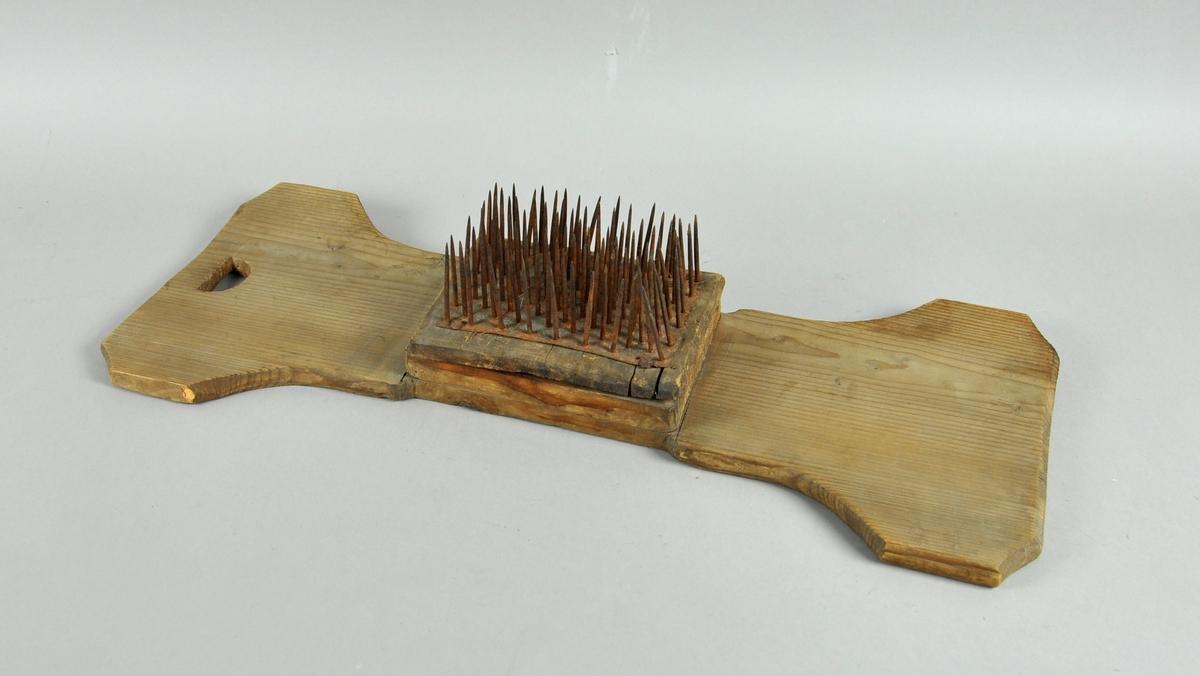 Linhekle i tre, med hull til håndtak i den ene enden. På midten av trestykket en kloss med stålnagler.