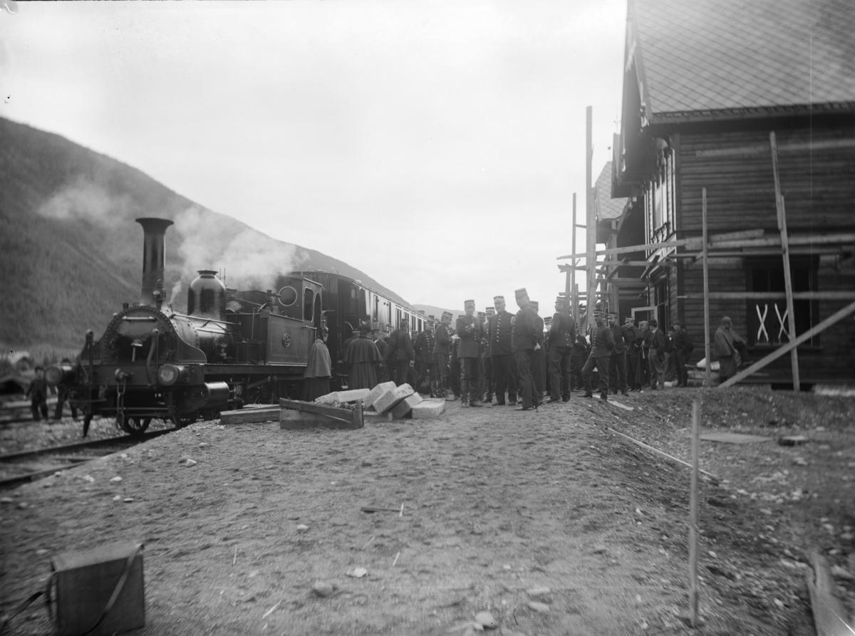 Togsett med lokomotiv og vogner på Otta stasjon. Mange personer med jernbaneunifor og andre personer. Før åpning av Otta staion.