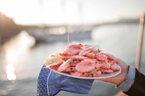 Hånd holder hvit tallerken med reker og med en blå serviett under, diffust seilskip i bakgrunnen.. Foto/Photo