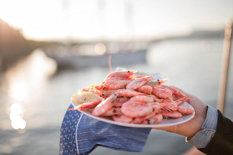 Hånd holder hvit tallerken med reker og med en blå serviett under, diffust seilskip i bakgrunnen. (Foto/Photo)
