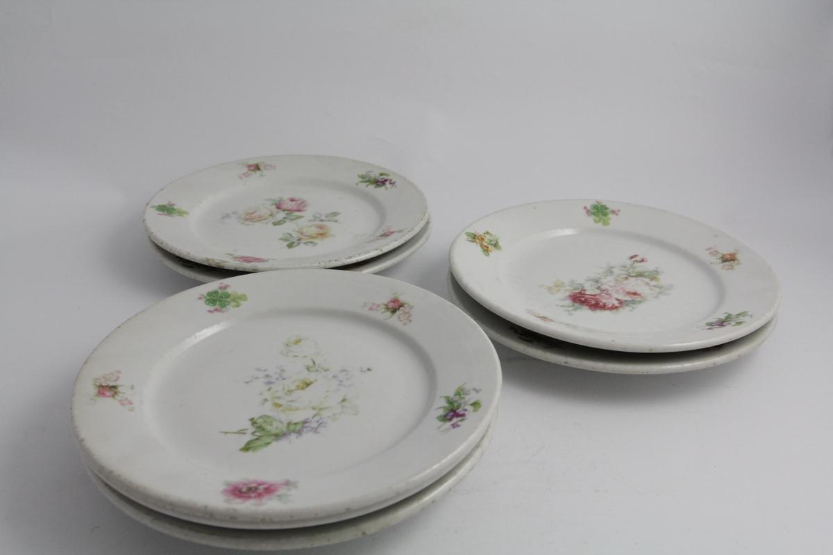 Runde tallerkener, syv stykker. Opphøyd kant på baksiden av fane. Hvit bunn, polykrom blomstermotiv trykket på. Hver tallerken er litt forskjellig. Blomsterbukket på speil, mindre buketter på fane.