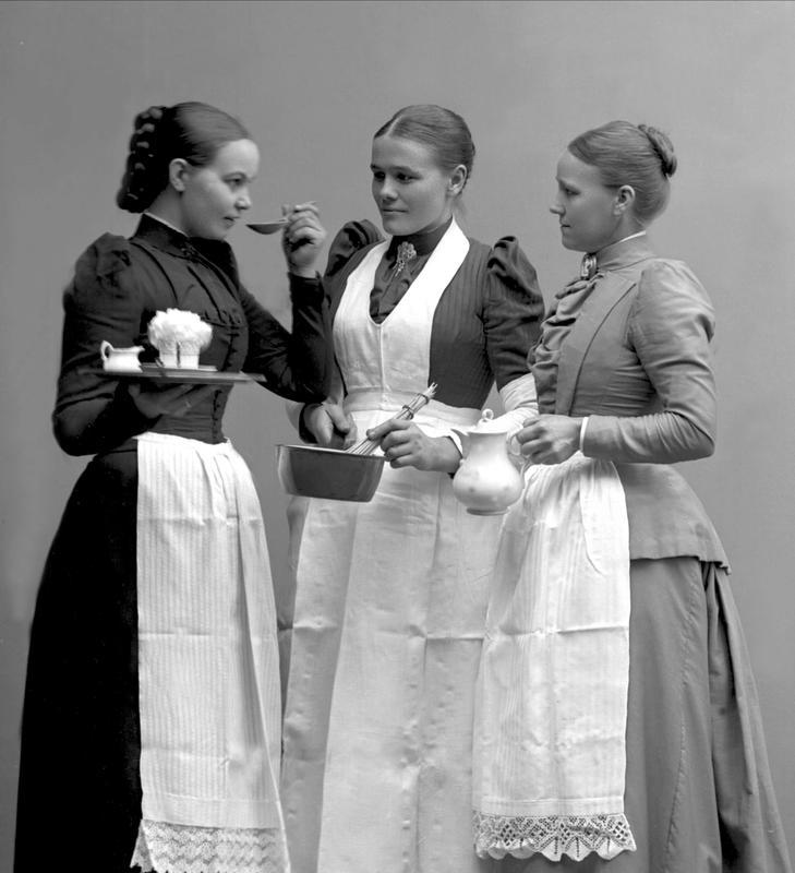 Dette arrangerte gruppeportrettet tatt i  fotograf Borgens atelier i Kristiania viser tre unge tjenestejenter i strøkne serveringsforklær. (Foto/Photo)