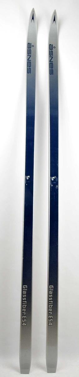 Langrennski laga av glasfiber, med såle av plast. Blå overside med striper og dekor i sølv. Det er bora hol til binding i den eine skia.
