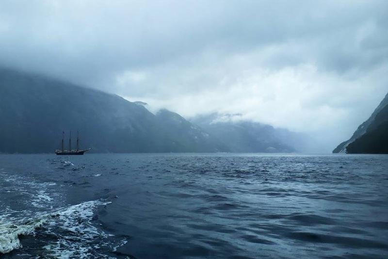 """Skonnerten """"Svanen"""" på Vestlandet, på dypblått vann, bratte fjellsider i bakgrunnen, overskyet."""