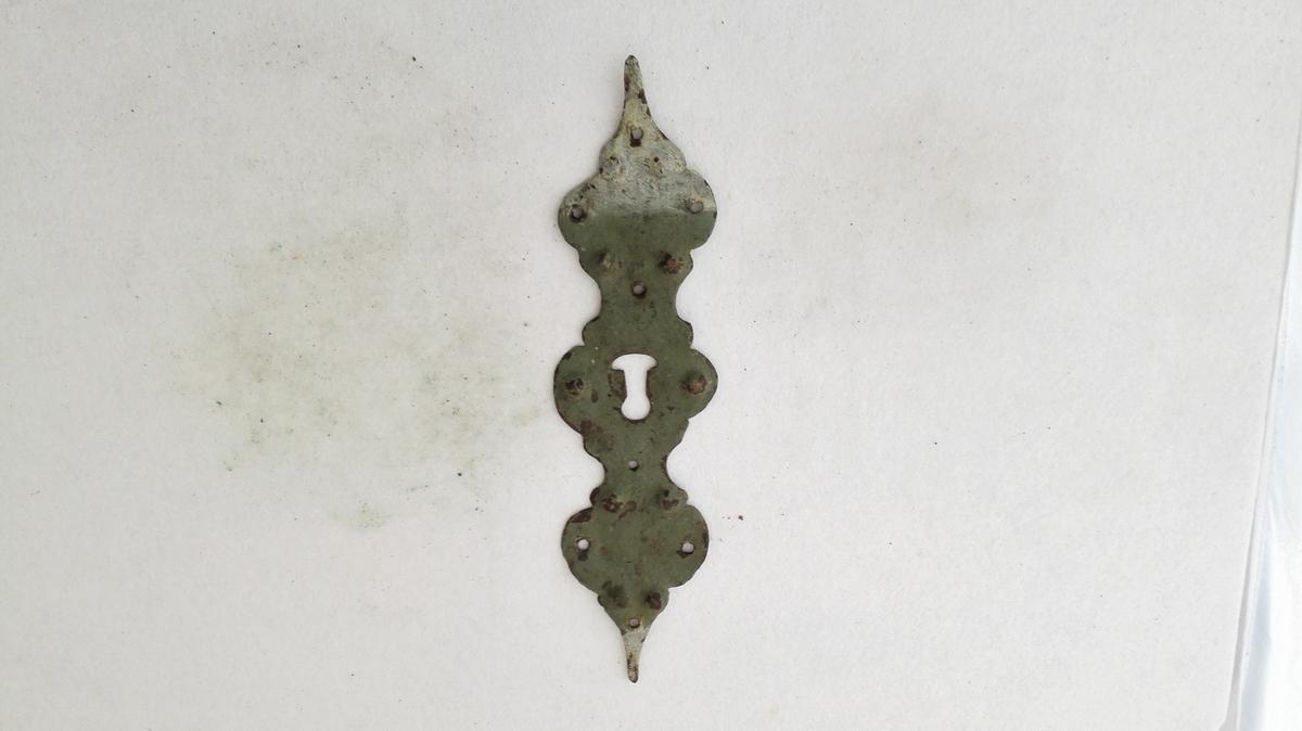 1 nökleskildt.  Profilert nökleskildt av jern, 29 cm langt, paa forsiden malt graagrön. Stammer fra et nedrevet hus paa Øvre Amble.  Gave fra G.F. Heiberg, Amble.