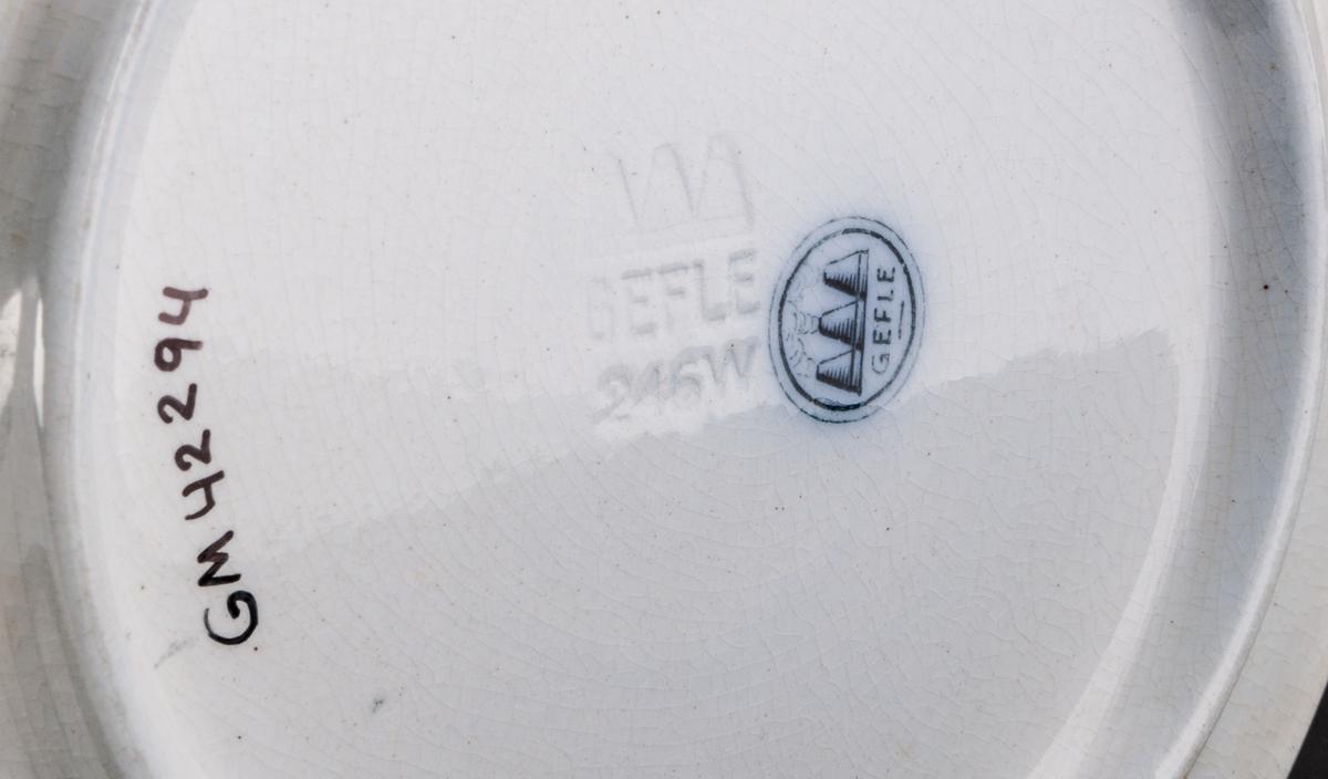 Jubileumstallrik i lergods, för utställningen i Gävle 1946. Vit med blå text och bild. Bild föreställande stadsmotiv. Tillverkad vid Gefle Porslinsfabrik. Försedd med hål och upphängningssnöre.
