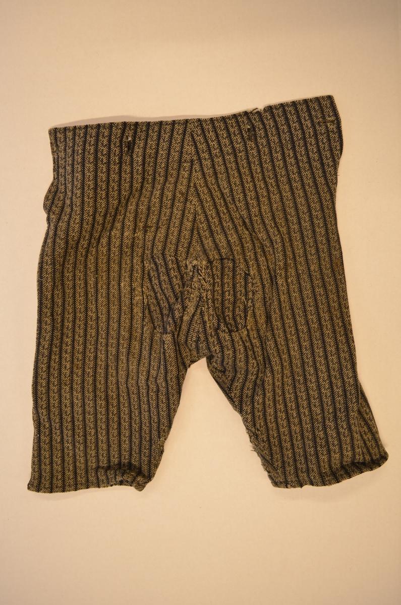 """Bukse til gutt i stripa ulltøy i blått og kvitt. Brok med """"klaff bak, fire knappehol på bakstykket. Fleire hol og lappar på kne og bak."""