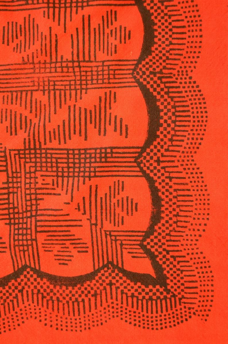 Sjal i raudt handvove ulltøy, påtrykt svart mønster. To av kantane er falda med svart tråd, dei to andre har jarekantar. Påsydde frynser i raudt og svart ullgarn i to av sidene. Fleire små hol.