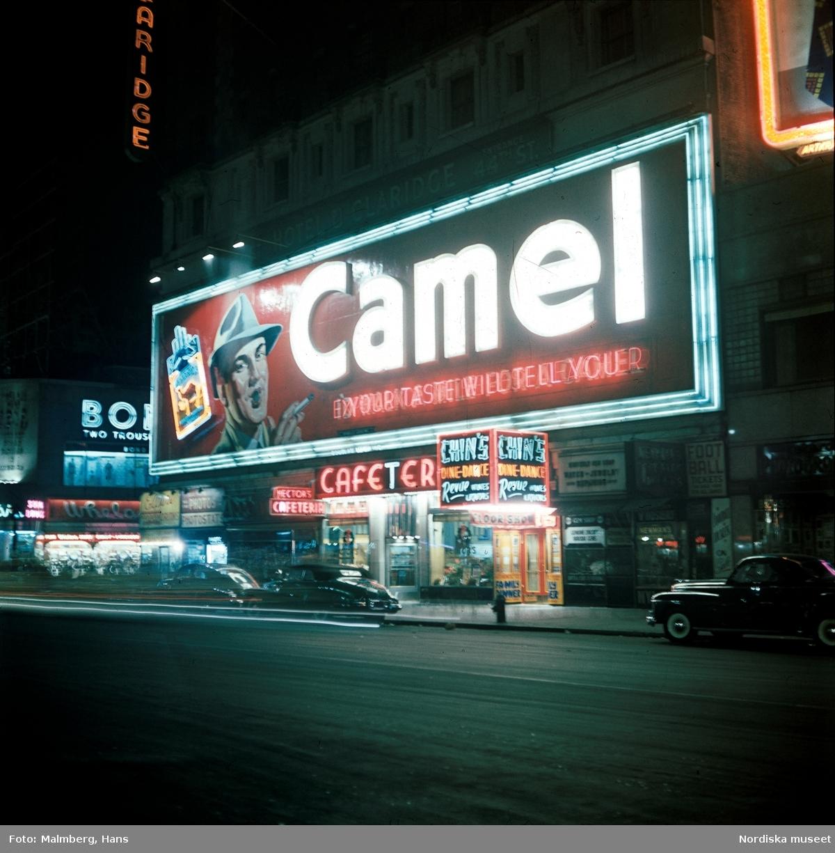 New York, USA. Gata i kvällsbelysning. Neonreklamskyltar för Camel-cigaretter etc.