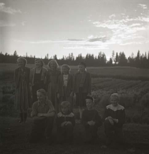 En grupp vuxna och ungdomar står uppställda framför en åker med grönsaksodling. Unga Odlare 1950.