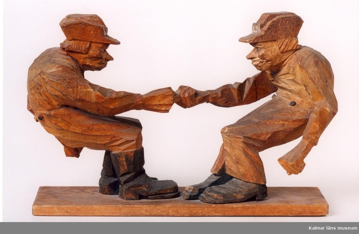 KLM 39255:11. Skulptur, av trä. Två gubbar som drar fingerkrok. Stövlar och knappar svärtade. Monterade på fotplatta. Signatur under fotplatta: C J Trygg 1917.