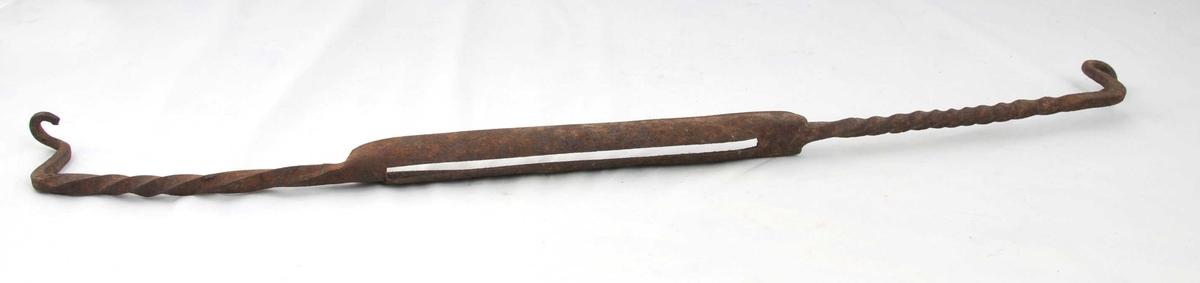 Smidd jern til skinnbearbeiding. Lang stong med dobbel kniv på midten. Mellom knivane er det ei slisse der avskrapa fett skulle kome ut. Frå kniven er stålet vridd. Endane av stonga er bøygd i rett vinkel og avslutta med festelykkjer til å montere på vegg. Rusta.
