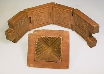 Fyrsidig smörform av furu med löstagbart toppigt lock. Sidorna är ledade och hopsatta med genomgående träplugg. Invändig dekor av karvsnitt i olika mönster. I ett av lockets hörn ett urtag för en träplugg.