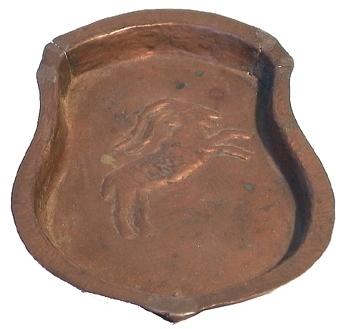 Askfat av koppar med kant runt om. I mitten en bild av en bock, motivet är pressat.