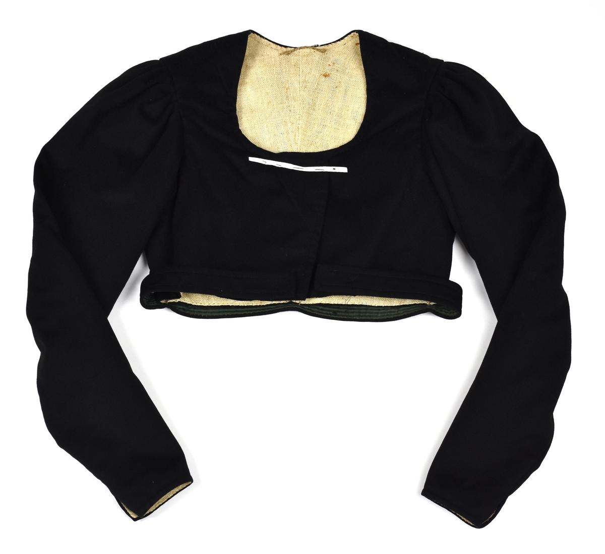 Tröja i svart kläde med foder av grovt linne (tovgarn). Tröjan har skärp i midjan som är fodrat med grönbrunrandigt bomullstyg.