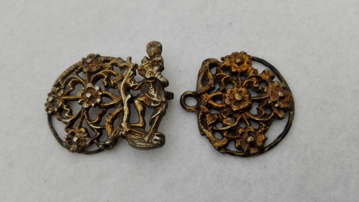 Form: Dobbel sølvspenne som framstiller St. Kristopherus, som berer Jesusbarnet over elva. Kjøpt i Bøfjord for 20 kr. 8/9 1904. Truleg middelaldersk.