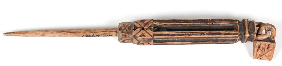 Utskuren och ornerad nystpinne, genombruten, innehållande en träkula med kvadratisk hänge.