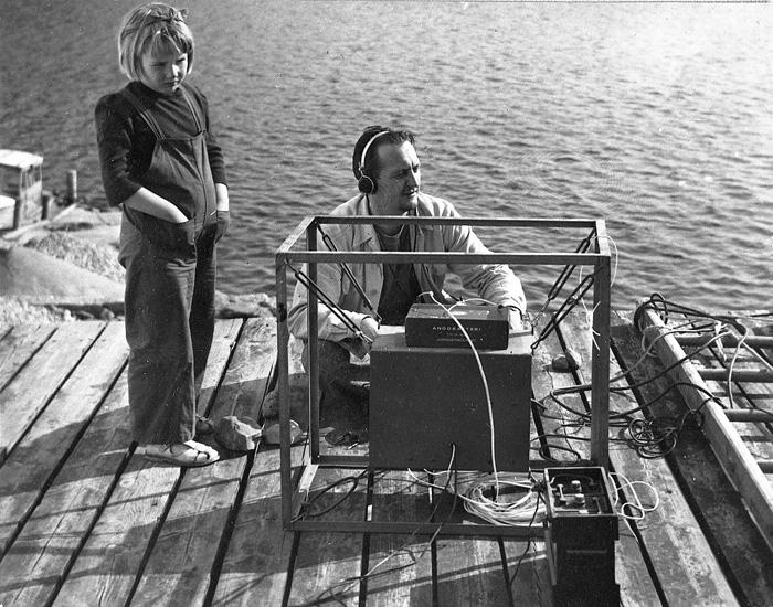 """Enligt uppgift: """"Experiment på bryggan med hydrofon år 1952. På bilden Anita Åkermo (7 år) och forskare Fritz Koczy""""."""
