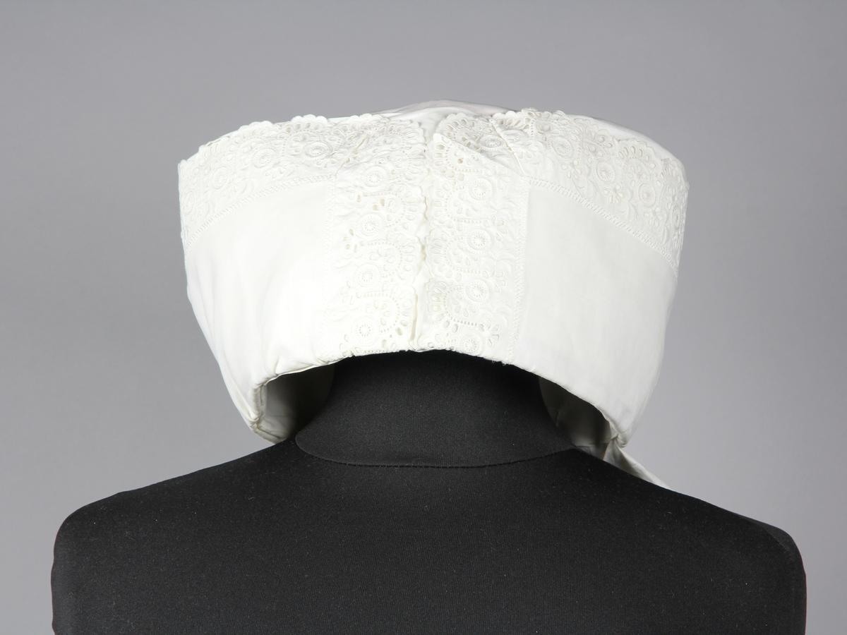 Huvudduk formad till klut. Buren till kvinnlig dräkt från Harjager i Skåne. Tunnt vitt bomullstyg med broderad hålspetts påsydd längs kanterna. Duken är konstfullt monterad i lagda veck och vridningar fastsatta med nålar på en bas av rött ylletyg. Duken samlas i nacken till ett nedhängand fång. Tyget är stärkt.