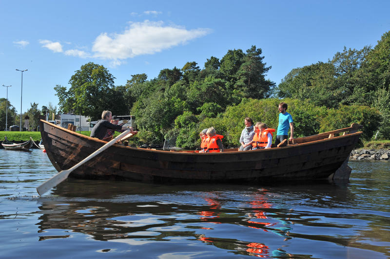 Trebåten Vaaghals på vannet med fire barn i redningsvest og tre voksne ombord, én ved roret, én ved årene.
