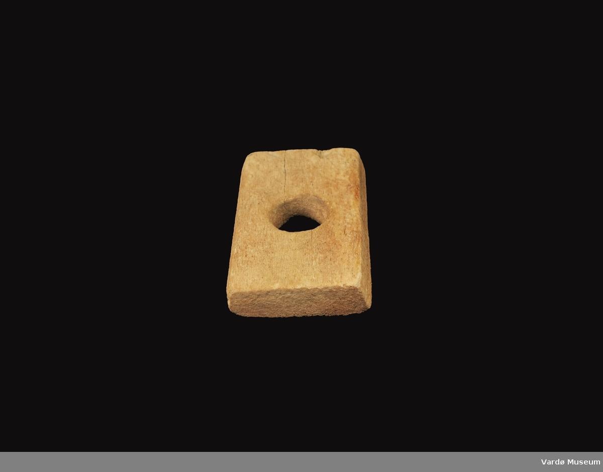Firkantet og porøs, hull i midten på ca. 2,5 cm i diameter.