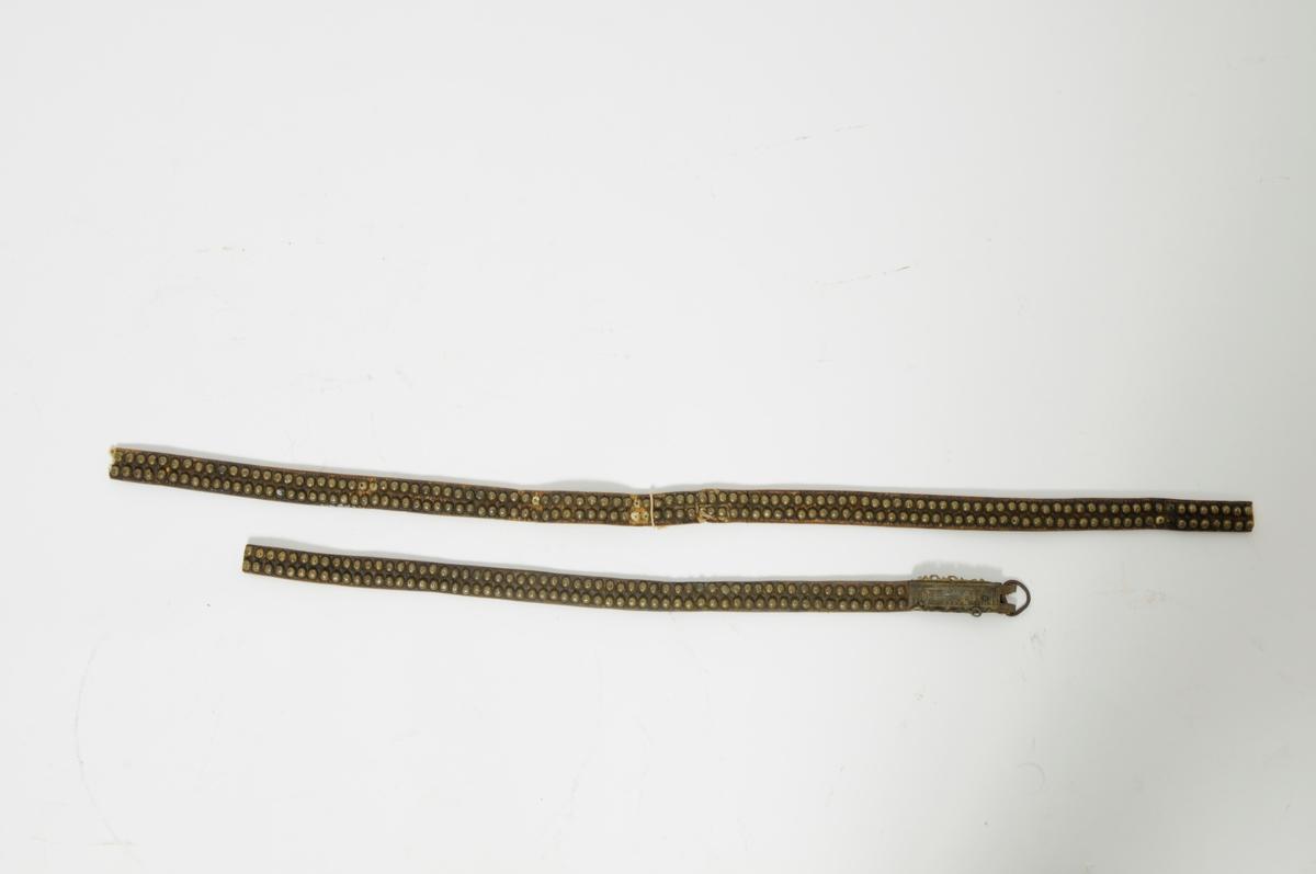 Naglebelte, tjukk lérreim med to tettsitjande rader med messingnaglar. Desse er klinka saman med ei tynn messingplate på baksida. I eine ende messingspenne med gravert dekor og ein rusta jernring. Belte er avskore så det er ingen spenne i den andre.