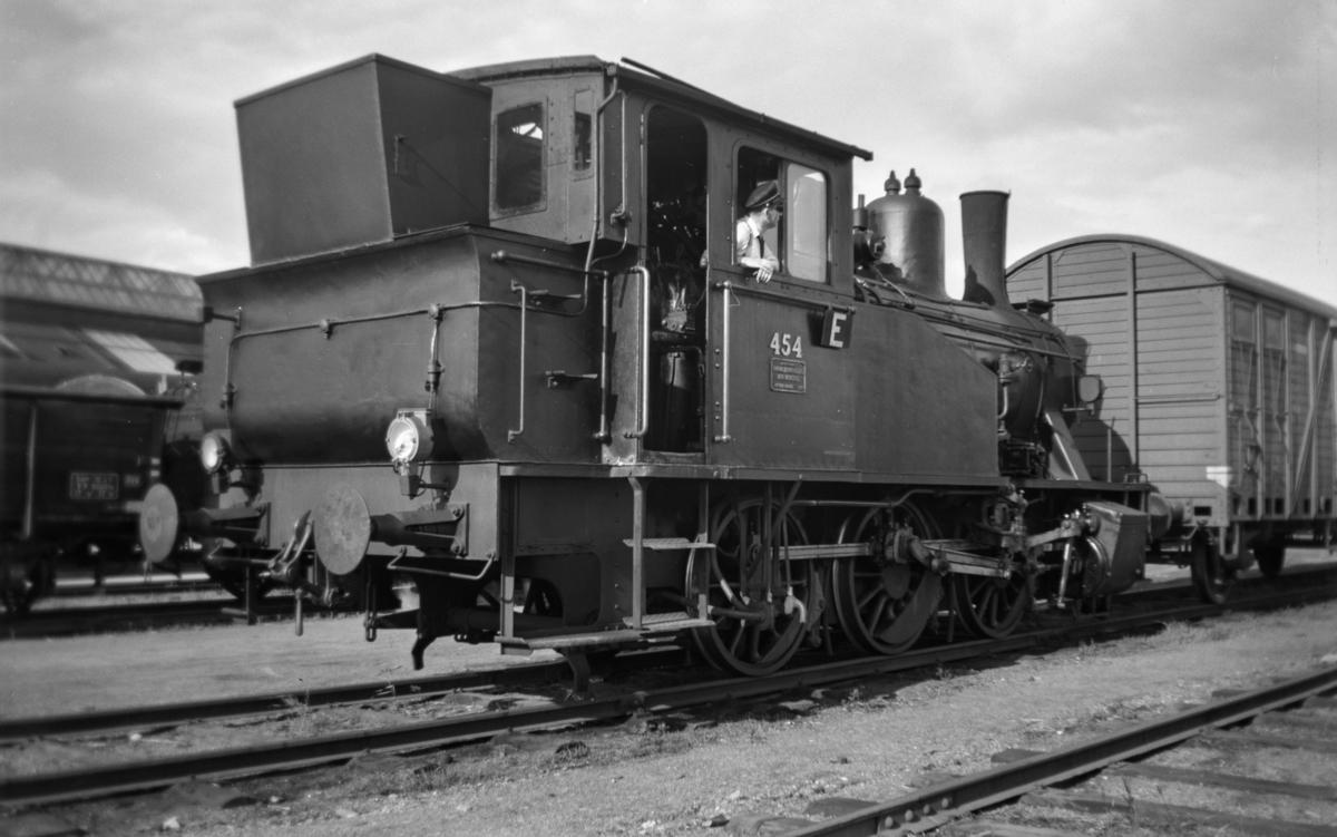 Damplokomotiv type 23b nr. 454 i skiftetjeneste på Trondheim stasjon. En fyrbøter tjenestegjør som lokomotivfører.