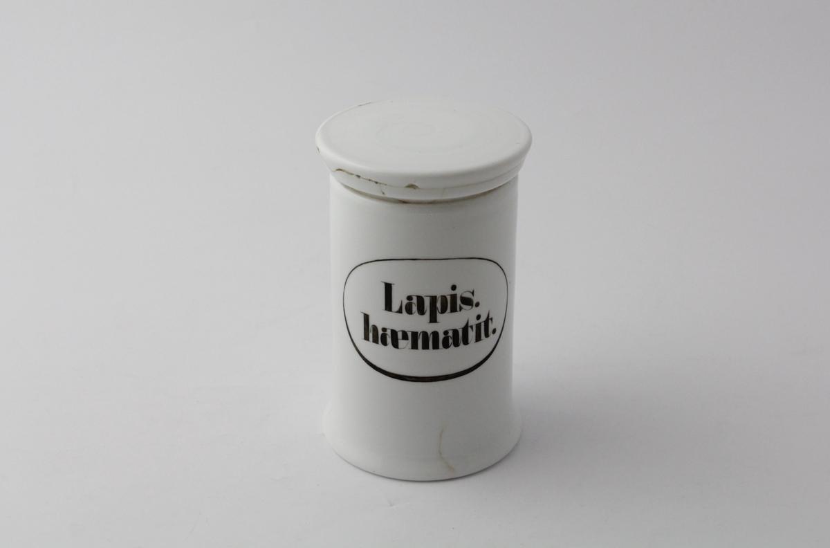 Hvit, sylindrisk porselenskrukke med rundt flatt porselenslokk. Sort påmalt påskrift med oval ring rundt. Brukt til oppbevaring av hæmatittsteiner, og inneholder noen slike.