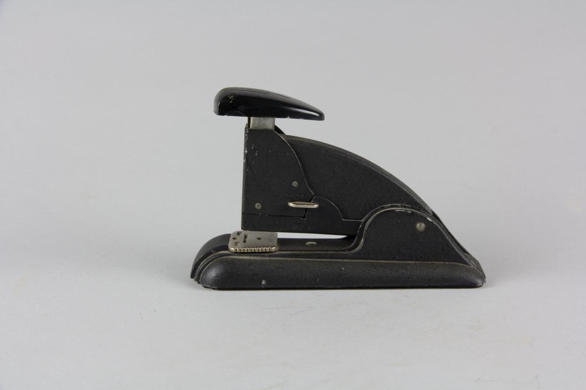 Häftapparat Speed Stapler tillverkad av svartlackerad metall. Avlång fotplatta med överdel. Tryckhandtag i plastmaterial högst upp. Innehåller ett fåtal häftklamrar.