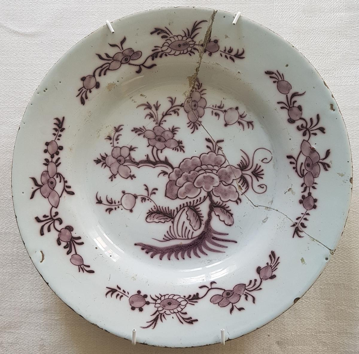 Hvitglasert tallerken med auberginefarget håndmalt blomsterdekor.