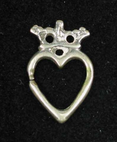 Lita støpt hjertesprette i sølv med krone. Det er tre hull i kronen som har en liten tapp øverst i midten. Tornen mangler. Ingen synlige stempel.