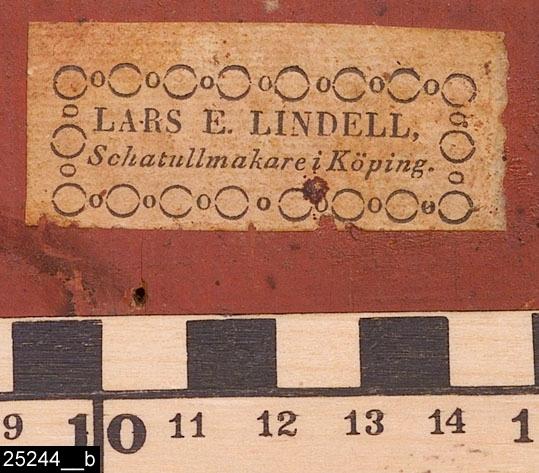 """Anmärkningar: Fällbord, Lars Eric Lindell, 1818-1843.  Oval bordsskiva med upphöjd kant. Två draglådor på sidorna med vardera en dragknopp av ben (bild 25244__d). Profilsvarvat ben. Tre S-formade fötter. Baktill finns en etikettsignering som lyder """"LARS E. LINDELL, / Schatullmakare i Köping."""" (bild 25244__b). Baktill är bordet rödmålat (bild 25244__d). H:1050 Br:640 Dj:445  Bordet går att fälla upp, höjden blir då 1050 mm. I nedfällt tillstånd är det 710 mm högt (bild 25244__c). Bordsskivan är fanerad med alrot, blindträet är furu. Alroten är fernissad. Benet och fötterna är av ljust lövträ och är också svärtade. Ett identiskt bord signerad LARS E. LINDELL finns på Köpings museum.  Mälardalen och framför allt städerna Arboga, Köping, Kungsör och Eskilstuna var under 1700-talets senare hälft och början av 1800-talet centrum för tillverkning av alrotsfanerade möbler och föremål. Här tillverkades bl.a. fällbord, byråar och olika sorters askar. Föremålen såldes inte bara inom mälardalen utan även till Stockholm och till andra länder. Det främsta namnet inom alrotsföremålsproduktionen är Jacob Sjölin (1737-1785). Alroten togs inte från alens rötter utan från stamansvällningar vid rötterna. I synnerhet vid Mälarens stränder har tillgången på detta sorts virke varit god. På slottet förvaras en kortkatalog, upprättad av f.d. antikvarie Carin Thorsén. Den upptar över 300 alrotsföremål tillhörande museer, privatpersoner etc.  Lars Eric Lindell (född?-1843), gick i lära hos sin äldre broder Anders Lindell (den senare levde mellan 1778-1829 och var snickarmästare i Köping 1804 till sin död) och blev snickaremästare i Köping 1818. Verksam till sin död.  Litteratur: Anette Glöde, Fanering med Alrot, Linköpings universitet/Carl Malmsten, 2001 Åke Nisbeth, Schatullmakare i Köping och Kungsör, Västmanlands fornminnesförenings årsskrift 1960 Torsten Sylvén, Mästarnas möbler : Stockholmsarbeten 1700-1850, Stockholm 1999 Birgit Wennerberg, Köpings snickarämbetes historia, Västmanlands """