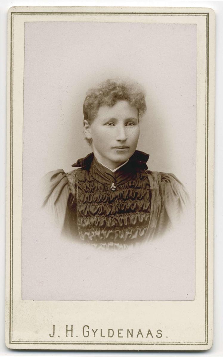 Studioportrett av en kvinne i kvartfigur.