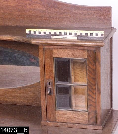 Anmärkningar: Spegelskänk, tvådelad bestående av spegeluppsats och skänk, ekfanerad, senjugend, omkring 1920.  Spegeluppsats: Svängd gavel med skurna blommor i ek (bild 14073__c). Skivan ovanför spegeln är profilerad och något indragen i mitten (bild 14073__b). Centralt placerad oval och fasettslipad spegel. Spegeln flankeras av två små skåp med blyinfattade och fasettslipade glas (bild 14073__b). Kombinerad nyckelskylt och handtag i koppar. H:500 Br:1230 Dj:270  Skänk: Framskjutande skänkskiva. Två draglådor med  kombinerad nyckelskylt och handtag i koppar. Pardörrar med försänkta speglar. I speglarna skurna blommor i ek, identiska med blommorna på spegeluppsatsen. Båda dörrar är försedda med kombinerade nyckelskyltar och handtag i koppar. Kontursågade nederdelar på fronten och sidorna. H:990 Br:1290 Dj:600  Tillstånd: Handtag på vänster skänkdörr saknas. Nyckel finns till skänken (bild 14073__d), men inte till spegeluppsatsens skåp.  Historik: Köpt på auktionshallen Biskopsgatan I, Västerås genom rustmästare Gustavsson.