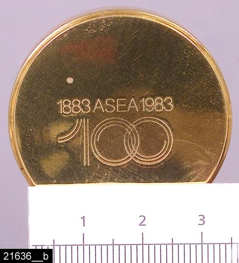 """Anmärkningar: Ljusstake, """"Misteln"""", 1983.  Rund fot med stämplar i form av en krona samt texten """"SKULTUNA 1607 I10"""", beteckningen I10 betyder att ljusstaken tillverkats 1983 (bild 21636__c). Armar i form av växtslingor. I mitten finns en platta med följande graverade text; """"1883 ASEA 1983 / 100"""" (bild 21636__b). Fyra klockformade ljushållare med manschetter undertill. Enligt en broschyr, utgiven av museet 2007 och benämnd """"Skultunastämplar 1800-2000"""", började den typ av stämpel som finns på föremålet användas 1922. Den användes fortfarande år 2007. H:290 D:120 Br:330  Tillstånd: Nyskick.  Historik: Inköpt för 430 kronor + moms 1983. Följande kommer från en äldre registrering av f.d. antikvarie Carin Thorsén 1995: När ASEA inför sitt hundraårsjubileum år 1983 beslutade att ge en gåva till alla anställda inom moderbolaget såg man sig om efter något annat vid sidan om den sedvanliga guldklockan. En kristallvas från Orrefors blev det andra alternativet och det tredje blev en ljusstake från Skultuna, en nyskapad modell men hämtad ur gammal formtradition. Modellen fanns tidigare, formgiven av Bror Johansson, f.d. gjutmästare i en verkstad i  Malmö, som gjort lampfötter, ljuskronor och en del annat. Ljusstaken är namngiven av försäljningschefen Jan Törnell, som sett till att den fått en misteldekor. Foten avslutas med en svarvad knopp, som är utbytbar, och den ersattes på ASEA- varianten av en rund platta med texten ASEA 100, 1883 - 1983. Beställningen blev en stor påfrestning för Skultuna Messingsbruk; den krävde mycket övertidsarbete och andra leveranser kom i kläm. ASEA hotade med böter om inte alla var klara i tid till jubileumsfestligheterna."""