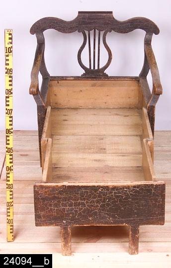 Anmärkningar: Stolsäng, Karl Johan, 1800-talets första hälft.  Pilbågeformat överstycke. Genombruten rygg med en lyrdekoration. S-formade bakstolpar och armstöd. Löstagbar sits av trä. Fronten går att dra ut, då får man en säng såsom på bild 24094__b, djupet blir då 1630 mm. Åtta ben varav de i hörnen är nedåt avsmalnande, de övriga är raka. H:890 Br:910 Dj:660  Hela möbeln är brunmålad och bär spår av naturligt slitage.  Tillstånd: Hjul saknas på två av frambenen. Färgen är starkt krackelerad.  Historik: Inköpt för 3500 kronor från Skultuna antik, december 1989, vilka köpt den på auktion i Högfors, Norberg.