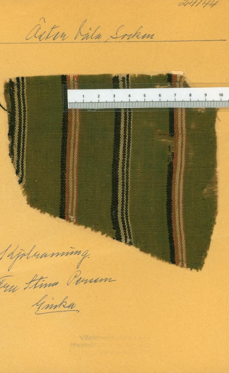 Anmärkningar: L; 133 B; 124       L; 187 B; 140 Vävprov av lin och ull, randigt. Varpen är av ofärgat lin. Inslaget av ull är randat i rött, svart och vitt på grön botten. Tidigare ägd av fru Stina Persson Ginka Östervåla. Insamlad och skänkt av Olga Anderzon Västra Bergsgatan 8 Västerås.