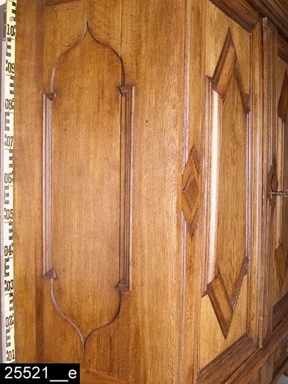 """Anmärkningar: Skåp på fot, barock, 1700-talets första hälft.  Överdel: Framskjutande profilerat rakt krön. Fasaden indelas genom tre lisener kring två spegelförsedda pardörrar med spetsvinkliga förkroppningar. På lisenerna är rektangulära och kvadratiska profilerade fyllningar applicerade. Ett listverk med profilerade gerade lister omger speglar, fyllningar, förkroppningar och lisener. Skåpets sidor har rektangulära nedbottningar med lökkupolformade avslut (bild 25521__e). Invändigt skedhylla och två hyllplan. Nedersta hyllplanet har undertill två draglådor (bild 25521__b). Hakar i järn som håller samman skåpets olika delar finns upptill och nertill på skåpets båda sidor. Lås i järn med inristad blom- och bladdekor (bild 25521__c), nyckel i järn (bild 25521__f). Dörrsnäppar i metall upptill och nedtill på höger dörr. H:1365 Br:1705 Dj:640  Underrede: Underredets sidor har rektangulära nedbottningar samt draglåda med tvådelad front. Lådfront med spetsvinkliga förkroppningar och päronformade mässingshandtag med stjärnformade beslag (bild 25521__d). Underredets fyra svarvade ben är stagade av ett kryss och försedda med kulfötter. H:675 Br:1600 Dj:620  Skåpet huvudsakligen i mörkbetsad ek. Ekfanér på lisener och lådfronter. Blindträ och bakstycke i furu.  Tillstånd: Bakstycke och delar av hyllplan utbytta. Dörrsnäppar senare tillkomna. Möjligen spår efter tidigare lås på höger dörr. Skåpet har möjligen varit med om en brand.  Historik: Gåva av Märta jansson, Solmyra 2:58, Kolsva. Enligt familjetraditionen har skåpet en gång tillhört och brukats av Ebba Brahe och man kallade det för """"Ebba Brahes skåp"""". Märta Jansson var född 1901 i gården Solmyra 2:3 och barn till Alfred Jansson och hans hustru Anna Matilda f Olsson, som var ägare till gården sedan 1898. Fadern var förutom hemmansägare även kommunalman och kyrkvärd. En bror till Märta, även han ogift, drev gården fram till 1900-talets mitt. Själv bodde hon sedan 1920 och till sin död i en nybyggd villa intill gårdens gam"""