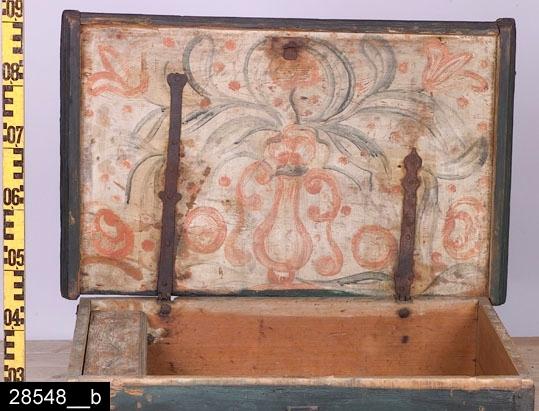 """Anmärkningar: Kista, 1700-tal.  Gångjärnsförsett platt lock med järnbeslag i hörnen. På kortsidorna finns järnhandtag och på framsidan en nyckelskylt i järn. Man kan också se en tidigare färg och påskriften """"Anno 1748"""". Invändigt en bemålad läddika längst till vänster (bild 28548__b). Insidan av locket är försett med ett blomstermåleri, bl.a. i form av tulpaner och blommor som prunkar ut från en vas. H:395 L:810 Dj:510  Invnr. 28548 var tidigare försett med invnr. 2679, vilken är en annan kista. Av den anledningen fick den på denna plats registrerade kistan ett nytt invnr. av projektet Access vid dess genomgång av bl.a. kistor 2007.  Tillstånd: Nyckel och lås saknas. Hela kistan är utvändigt ommålad. Det finns fyra hål i hörnen på botten. Dessa är avsedda för fötter (som saknas)."""
