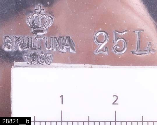 """Anmärkningar: Kittel, 1940-tal.  Rund kittel med två handtag och ett handtagsförsett lock. Översta tredjedelen av kärlet är polerat. Runt det ena handtaget hänger en lapp med texten """"SKULTUNA BRUK GRUNDLAGT ÅR 1607"""". Till höger om det ena handtaget finns stämplar i form av en krona samt texten """"SKULTUNA 1607 25L"""" (bild 28821__b). Kitteln är avbildad i kataloger från Skultuna från 1940-talen. I en katalog från 1943 framgår det att kitteln kostade 99 kronor (bild 28821__c). Kastrullen är mycket tung och uppges vara tillverkad av hardalplåt (bild 28821__c-d). H:330 D:255 Br:460 (avser måttet diameter samt handtagens mått)  Tillstånd: Nyskick.  Historik: Gåva från SAPA AB, Division Service, 2002. Föremålet stod i ett skyddsrum på bruksområdet i Skultuna."""