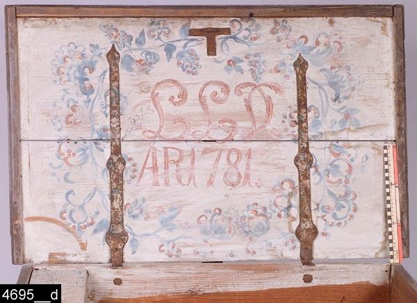 """Anmärkningar: Brudkista, målad datering 1781.  Gångjärnsförsett platt lock med järnbeslag i samtliga hörn. Lockets kanter är profilerade. Kortsidorna är försedda med järnhandtag. Fronten har konturerade hörnbeslag. I frontens mitt finns en nyckelskylt av järn och på sidorna om denna järnbeslag som är volutformade upptill. Invändigt finns en avskiljare i botten samt en läddika som är bemålad både utvändigt och invändigt (bild 4695__b-c). På insidan av locket är en blomsterkrans samt frukt- eller bärliknande dekorer målade (bild 4695__d). I mitten finns det målade monogrammet """"LLD"""" samt årtalet """"ÅR 1781"""". Hela kistan är grönblåmålad och naturligt sliten. H:595 L:1020 Dj:665  Tillstånd: Nyckel saknas.  Historik: Inköpt från hemmansägare Johan Ålund, Svedberget, Västanfors, 1925."""