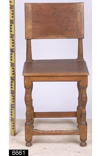 Anmärkningar: Stol, s.k. åttaslåstol (benämning efter antalet benslåar), omkring 1800.  Rektangulär ryggbricka med de brännstämplade initialerna FA (Fredrik Adolf) samt en hertigkrona. Även initalierna CL (jämför bild 6658__c). Raka bakstolpar. Sits av trä. Under sitsen finns de brännstämplade bokstäverna V.R.Off.K. (Västmanlands Regementes Officers Kår, jämför bild 6658__d). Samtliga sargar är avfasade i nederkanterna. Fyra fotslåar. Fyra profilsvarvade ben med runda fotavslutningar (jämför bild 6658__b). H:935 Br:445 Dj:405  Observera att bilderna är attribuerade till den identiska stolen med invnr. 6658. Hela stolen är av furu utom bakstolparna och frambenen som är av ljust lövträ. Främre fotslån är naturligt nött.  Tillstånd: Stolen är renoverad, senare bets eller annan ytbehandling. Små sprickor i samtliga fotavslutningar.  Historik: Tillhört Gustav III:s broder Hertig Fredrik Adolf som var chef för Västmanlands regemente från 1780-1801. På Salbohed bodde Hertig Fredrik Adolf i en paviljong vari denna möbel fanns. Hertigens paviljong är flyttad till Sätra Brunn. Gåva från I 18:s officerskår.