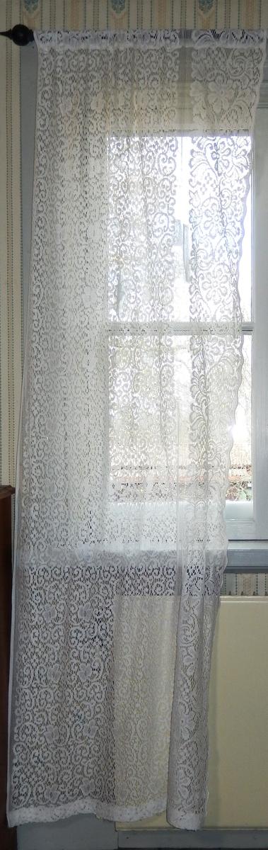 Spetsgardin, vit, av bomull med genombrutet mönster. Framkanten med udd. Kanal för gardinstång.