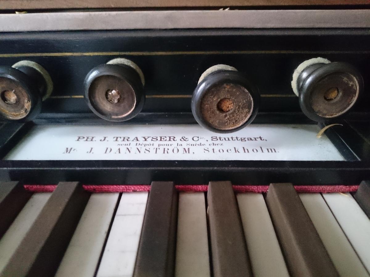 Orgel, tramporgel, harmonium, rektangulär av trä med valnötsfanér.  Vikbart lock och löst notställ. Undertangenter av ben, övertangenter av ebenholts. 12 andrag (skyltarna saknas). Svarvade pelare bär upp övre delen med klaviaturen. Två trampor.