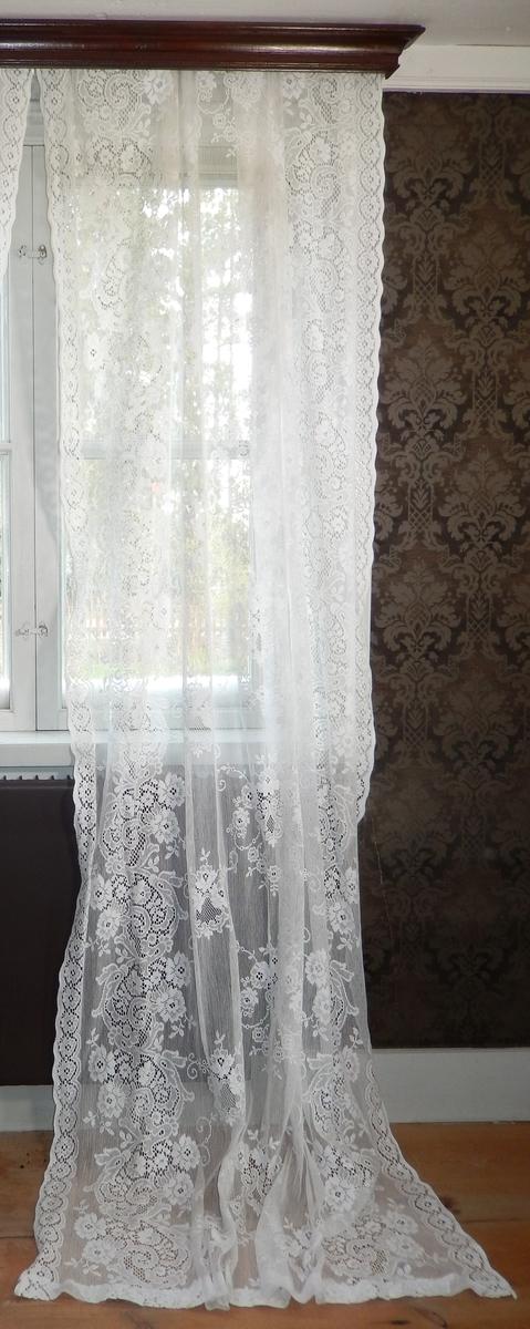 Spetsgardin, vit, av bomull med genombrutet mönster. Kantudd.