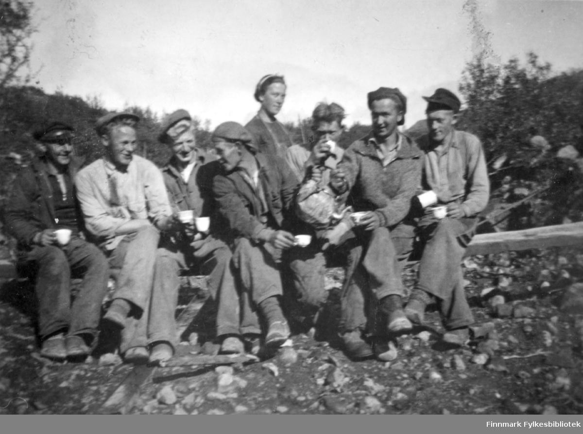 """""""Fra vegarbeidsdagene ved Hauksjøen, 1939"""". Gruppebilde av veiarbeiderne som har kaffepause. Familiealbum tilhørende familien Klemetsen. Utlånt av Trygve Klemetsen. Periode: 1930-1960."""