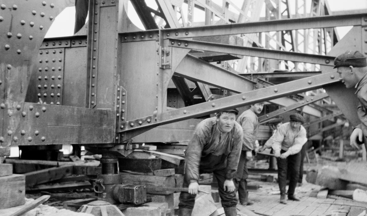 Ombygging av jernbanebrue ved Fetsund i Akershus, antakelig i 1916.  Fotografiet viser tre arbeidere som later til å være i ferd med å justere høyden på det som ser ut til å være brukonstruksjonens hovedspenn ved hjelp av hydrauliske jekker.  Posisjonen støttes opp ved hjelps av tømmerstokker og trekiler.  Karene er kledd i busseruller og sixpenceluer.  Brukonstruksjonen over dem er sammenklinket av støpejernskomponenter.   Den første jernbanebrua ble ved Fetsund ble bygd i perioden 1860-62 i forbindelse med anlegget av Kongsvingerbanen.  Herreddstyrene i Fert og Høland bidro med 500 spesidaler hver for å få et vegfelt ved siden av jernbanestraseen.  Vegfeltet ble plassert på nedstrøms side av jernbanelinja.  Det skulle være framkommelig for vanlig hestetrafikk.  I 1909 ble det lagt fram planer om å bygge en vegbane også på motstrøms side, slik at en kunne unngå problemer ved møtende ferdsel.   I store flomår hadde tømmeret lett for å hope seg opp på oversida av brua.  De trange åpningene mellom brukarene var en av årsakene til at Christiania Tømmerdirektion på denne tida valgte å flytte sorteringslensa fra Bingen i Sørum til Fetsund i Fet.  Storflommen i 1910 (jfr. SJF. 1989-02570-02571) bidro til at planene om en ny brukonstruksjon vant aksept, planer som altså var i ferd med å bli realiserte da dette fotografiet ble tatt.